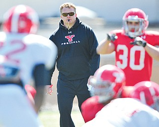Youngstown State head coach Eric Wolford watches both the offense and defense during a spring practice session at Stambaugh Stadium. He will be watching more closely tonight when the Penguins play their annual Red & White game at Stambaugh.