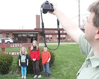 William Harris takes a photo of his niece Emily Orlaski, a second-grader at Lloyd Elementary in Austintown, daughter Hannah Harris, a sixth-grader who attended Lloyd, and son Matthew Harris, a third-grader at Lloyd. An open house took place Wednesday for students, teachers and alumni to gather and say farewell to their school.