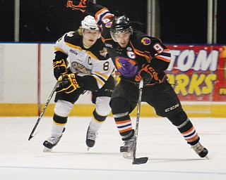 Phantoms forward Austin Cangelosi (9) skates away from Green Bay's Sheldon Dries (8) during Sunday's game at the Covelli Centre.