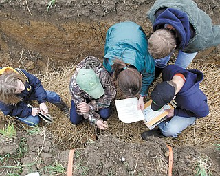 Students get dirty, left, examining soil characteristics Wednesday during the 2013 Northeast Ohio High School Envirothon at Mill Creek MetroParks Farm.