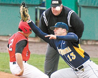 YSU's Mike Accardi makes it back to first base as West Virginia's Ryan McBroom misses the ball in a pickoff attempt during Wednesday's game at Eastwood Field in Niles. Accardi advanced to third on the error, but the Penguins came up short, losing 7-6.