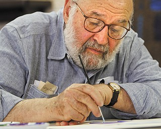 Mordechai Rosenstein concentrates on starting a painting focusing on Israel and related elements during an open house Thursday at Temple El Emeth in Liberty. The artist uses the Hebrew alphabet as his inspiration, incorporating bright colors and various shapes to convey a theme.