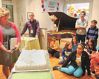 Becky Keck, director of Youngstown State University's SMARTS — Students Motivated by the Arts — and a groups of SMARTS students gather around a cake Thursday to celebrate the program's 15th anniversary.