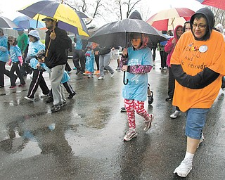 "Pam Wells, right, of Kinsman walks with her granddaughter, MacKenzie Collins, 8, during the ""Pound the Pavement for Autism"" walk Sunday in Howland Township Park. Wells was walking for her grandson, J.J. Juhasz, 7, a student at the Rich Center for Autism."