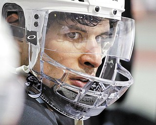 Pittsburgh Penguins' Sidney Crosby sits on the bench watching a power play drill during hockey practice in Canonsburg, Pa., Tuesday. Crosby has not been cleared to return to action since being hit in the face with a puck.