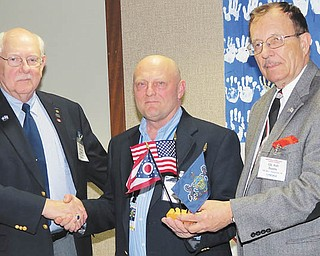 SPECIAL TO THE VINDICATOR During a recent combined meeting of the Military Officers Association of America and Reserve Officers Association in Vienna, Chief Warrant Officer Don Oglesby, left, secretary of Mahoning and Shenango Valley Chapter MOAA, with Col. Walter Duzzny, right, president of ROA, present a flag set to Dan Dickten, aviation director at Youngstown Airport and U.S. Army veteran.