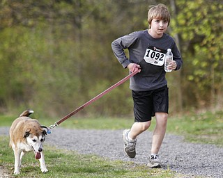 MADELYN P. HASTINGS | THE VINDICATOR  Evan Milford, 11, of McDonald runs with his German Shepherd Beagle mix, Gabby during the 1st annual Tails on Trails 5K walk at Austintown Township Park. All proceeds benefit Friends of Fido Mahoning County Dog Pound.