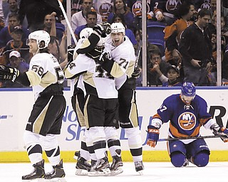 A dejected Andrew McDonald of the New York Islanders hangs his head while Pittsburgh's Chris Kunitz (14), Kris Letang (58) and Evgeni Malkin (71) celebrate the Penguins' win in Game 3 of the Stanley Cup Playoffs Eastern Conference quarterfinals Sunday at Nassau Veterans Memorial Coliseum in Uniondale, N.Y. Kunitz scored the winning goal in overtime to lift the Penguins over the Islanders 5-4 and give them a 2-1 lead in the series.