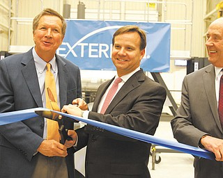 Ohio Gov. John Kasich, left, helps Brad Childers, Exterran chief executive officer, cut a ribbon at the company's new plant on Salt Springs Road. At right is Tom Humphries, head of the Youngstown/Warren Regional Chamber.