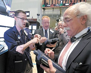 Specialist Bradley Kessler, left, works with traders on the floor of the New York Stock Exchange on Tuesday. The Dow Jones industrial average punched through another milestone Tuesday: its first close above 15,000.