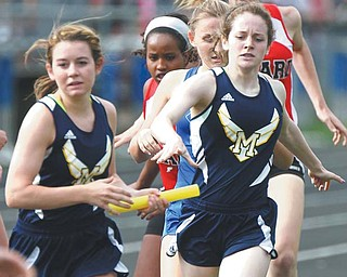 McDonald's Bailee D'Amore, left, takes the baton from her sister Abby D'Amore in the 4x800 relay on Tuesday during the first day of the Trumbull County Track and Field Meet at Lakeview High School.