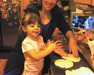 Angela and Sophia Testa are having fun making pizza.