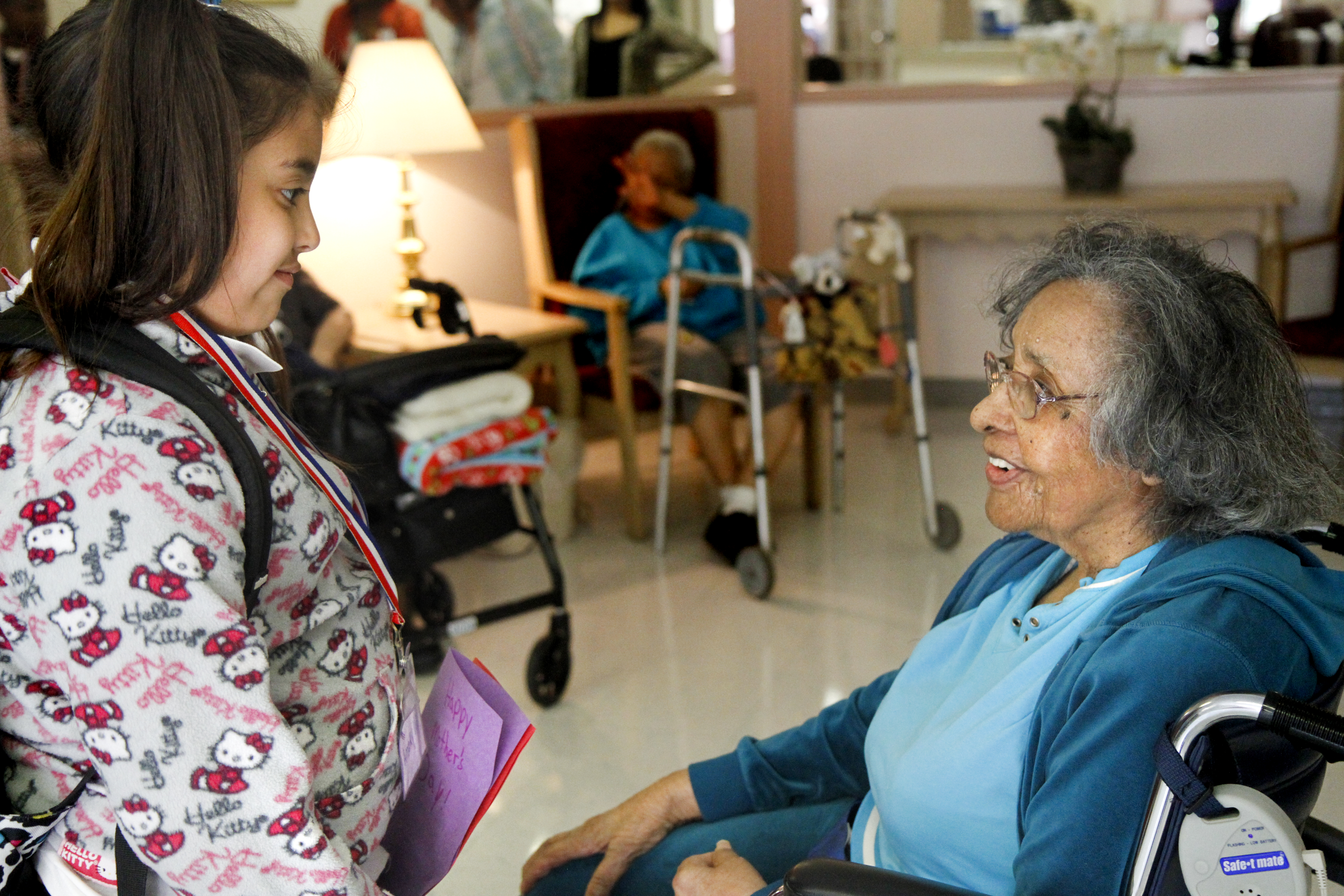 MADELYN P. HASTINGS   THE VINDICATOR   (L-R) Third grader in the afte rschool program at Martin Luther King Elementary, Amaryllis Rivera, gives a Mother's Day card to Metlean Singleton, resident at Danridge Nursing Home in Youngstown. The kids involved with the after school program presented the ladies of Danridge Mother's Day cards, songs and poems.