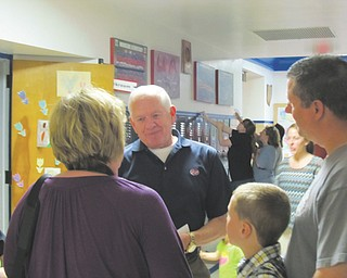 Dr. Tom Stellers, center, talks to attendees at Woodside Elementary School's farewell open house Thursday in Austintown. Stellers, now a member of the Austintown Board of Education, was a student when the school opened in the late 1940s.