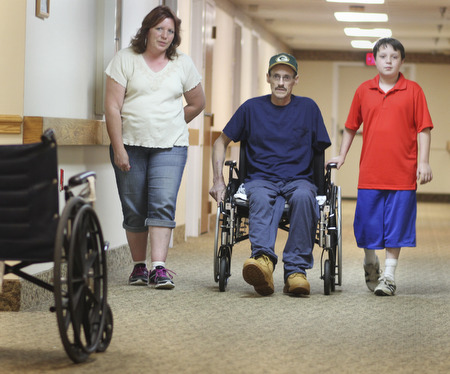 William D. Lewis\The Vindicator.William D. Lewis\The Vindicator William D. Lewis\The Vindicator Russell Marshall of Berlin Center his son Jacob, 11, and wife Melissa Marshall in a hallway at Canterbury Villa in Alliance where Marshall is undergoing rehabilitation after a March farming accident..He lost his arm and suffered horrific injuries in the accident.