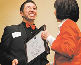 Denise DeBartolo York presents Logan Foster from East Palestine High School with a plaque marking his receipt of a scholarship from the Edward J. DeBartolo Memorial Scholarship Fellowship. Eight students received the scholarships totaling $56,000 at a Thursday luncheon at the Holiday Inn in Boardman.