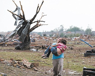 A woman carries her child through a field near the collapsed Plaza Towers Elementary School in Moore, Okla., after a monstrous tornado at least a half-mile wide roared through the Oklahoma City suburbs Monday.