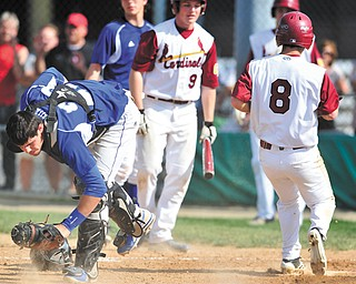 Poland catcher Nick Andrews, left, reacts after Cardinal Mooney's Drew Wollet (8) scored on an error during a Division II district semifinal Monday at Cene Park in Struthers. The Cardinals edged the Bulldogs, 9-8.