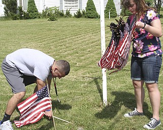 William D. Lewis\The Vindicator Austintown NHS members Camran Rezapourian and Lynnette Seebacher place flags at Edinburg and Ayrshire in Austintown.