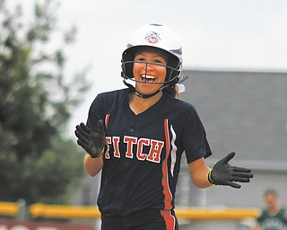 Fitch's Cali Mikovich is all smiles as she rounds the bases after hitting a two run home run against Aurora in the Division I district softball championship Wednesday at the Fields of Dreams in Boardman. The Falcons ousted the Greenmen, 5-2.