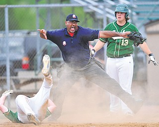 Ursuline batter Sam Donko (13), right, watches as the home plate umpire calls teammate Ryan Strollo out after Strollo attempted to score on a passed ball during the Division III district baseball championship against South Range on Wednesday at Cene Park in Struthers. The Irish downed the Raiders, 12-1.