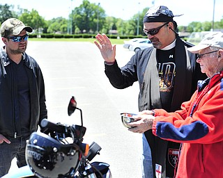Reverend Jeff Baker (center) blesses the Harley Roadster of Jeremy Redmond (left) of Brookfield. Richard Bess (right) of Howland holds a bowl of holy water for the blessing.