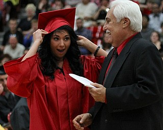 .IMG 9284: ÊAlicia Leone catches her cap before it falls off while receiving her diploma from Board of Education president Ron CarcelliÊduring commencement at the Struthers Field House on Sunday. ÊDustin Livesay Ê| ÊThe Vindicator Ê5/26/13 ÊStruthers High School. Ê