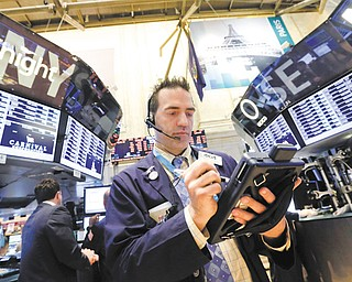 Trader Gregory Rowe works on the floor of the New York Stock Exchange on Tuesday. A jump in home prices helped send the stock market higher.