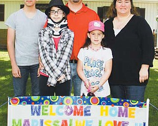 "Edward, Marissa, Ed, Mary Anne and Anne Marie Salus pose for a picture behind a ""Welcome Home"" sign set up for 12-year-old Marissa when she returned from the Cleveland Clinic after nearly three weeks and two surgeries to treat her chordoma."