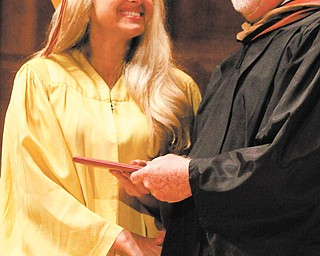 Sabrina Saadey smiles at Cardinal Mooney High School Principal John Young as she receives her diploma at Sunday's Stambaugh Auditorium commencement. Saadey was one of 136 seniors to graduate from the Roman Catholic high school.