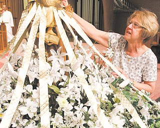 Kathy Rimedio, a member of St. Anthony of Padua Church, 1125 Turin St., Youngstown, decorates the statue of the patron saint with white and gold roses. A Feast Day Mass will take place at 6 p.m. Thursday followed by a festival with food and music. The statue will be featured in an outdoor procession at the event.
