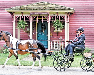 "Janet Yosay and Pat Moore of Canfield drive a bird-in-hand Eagle carriage pulled by ""Scout,"" a paint/Welsh cross pony in front of the Old School House in Zoar. It was built in 1836. Zoar is about 80 miles southwest of Youngstown."