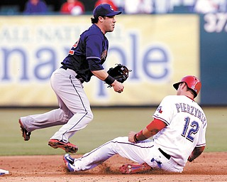 Cleveland Indians second baseman Jason Kipnis (22) jumps as Rangers baserunner A.J. Pierzynski (12) slides into second base on the double play during the third inning of Tuesday's game in Arlington, Texas. Nelson Cruz was out at first.