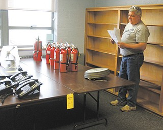 Jim Long of Austintown takes stock of fire extinguishers and phones at Lloyd Elementary School in Austintown. Along with Lloyd, two other schools in Austintown have an online auction of items for sale. Today was visitation day when items could be viewed in person.