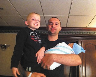 Kevin Cibula of Leetonia is holding his 5-year-old son, Ethan, and his other son, Jase, who was just born on Mothers Day.