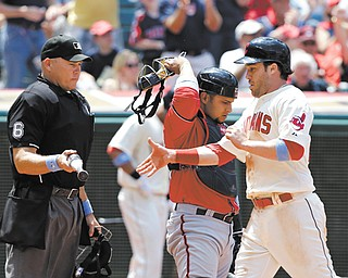 Indians baserunner Jason Kipnis, right, takes a bat from home-plate umpire Mark Carlson after scoring on a single by Carlos Santana in the fourth inning of Sunday's game against the Nationals at Progressive Field in Cleveland. The Indians won 2-0.