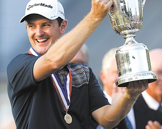Justin Rose of England celebrates with the trophy after winning the 113th U.S. Open golf tournament at Merion Golf Club on Sunday in Ardmore, Pa.