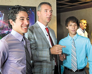 """Ohio State football coach Urban Meyer talks with Andrew Wollet, 17, left and his brother Alex Wollet, 14, both of Poland, during the United Way's """"Champions Among Us"""" dinner Monday at the Covelli Centre in Youngstown. Meyer was the keynote speaker at the event, which is the agency's biggest fundraiser."""