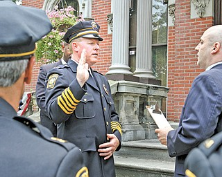 Eric Merkel, Warren's new police chief, is sworn into office Tuesday by Enzo Cantalamessa, city safety-service director, during a ceremony outside city hall.