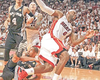 The Heat's LeBron James collides with the Spurs' Tim Duncan under the basket during the second quarter
