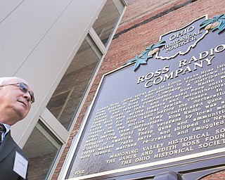 James H. Sisek, Mahoning Valley Historical Society member and capital campaign co-chairman, helps to unveil an Ohio Historical Society marker Tuesday at the Tyler Mahoning Valley History Center.