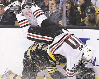Blackhawks center Patrick Sharp (10) is upended along the wall by Bruins defenseman Johnny Boychuk during the third period of Game 4 of the NHL Stanley Cup Final on Wednesday in Boston. The Blackhawks needed overtime again to down the Bruins, 6-5, and even the series, 2-2.