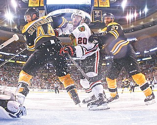 Boston Bruins defenseman Dennis Seidenberg (44) and center Patrice Bergeron (37) check Chicago Blackhawks left wing Brandon Saad, center, in front of the goal during the second period in Game 6 of the NHL hockey Stanley Cup Finals on Monday in Boston.