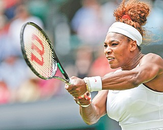 Serena Williams returns the ball to Mandy Minella during their first-round match Tuesday at the All England Lawn Tennis Championships in Wimbledon, London. Williams won, 6-1, 6-3, extending her winning streak to 32 matches.