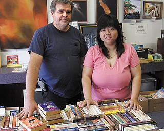 Richard and Ivy Sheeler stand next to a pile of paperbacks inside Bound 2 Read, their bookstore that opened last month on Elm Street in Struthers. The Sheelers, who own the building, decided to open the bookstore to sell the thousands of books they acquired at an auction and to promote reading for all ages.
