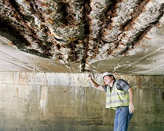 Randy Partika, Mahoning County bridge engineer, checks the underside of the structurally deficient, 1925-vintage Walker Mill Road Bridge over Yellow Creek in Boardman, where concrete is peeling and the bottom layer of reinforcing bars is exposed and rusting. The bridge carries a daily average of 1,880 vehicles and has a truck weight limit reduction.