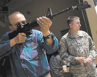 Marty Greggo of Austintown practices target shooting Sunday with Army Specialist Sean Clancy, from Akron, during the Ohio Army National Guard B Co., 237th Brigade Support Battalion open house.