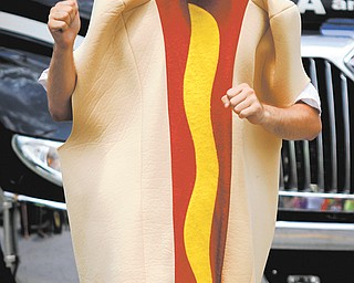 Chris Petri dances in his hot dog costume during Harry Stevens Hot Dog Day. The event included a parade, music and wiener-dog races.