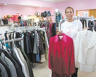 Sharetta Stokes shows two of the clothing selections available at her new business, Ms. Charolette's 'Resale' Boutique. Stokes named the consignment store in honor of her late sister, Charolette Stokes Ware, who died of breast cancer in 2012. The store also hosts a monthly breast-cancer support-group meeting.