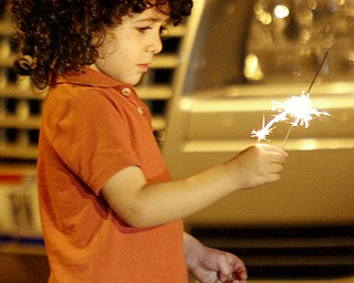 MADELYN P. HASTINGS | THE VINDICATOR  Albara Jwayyed, 3, of Katy, Texas holds a sparkler before watching the firework display shot from the Covelli Centre in downtown Youngstown on July 4, 2013.